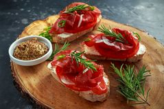 Salted bresaola beef, Italian bruschetta with soft chees, onions, whole grain mustard, chillies and fresh rosmary. Royalty Free Stock Photo