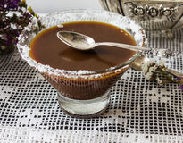 Salted caramel in a glass plate. dry flowers. silver spoon. Royalty Free Stock Photography