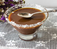 Salted caramel in a glass plate. dry flowers. silver spoon. Royalty Free Stock Image