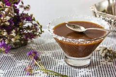 Salted caramel in a glass plate. dry flowers. silver spoon. Stock Photography