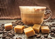 Salted Caramel Latte. Surrounded by coffee beans, caramels, and sea salt. Shot from a side view with selective focus and a rustic gingham background Stock Images