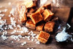 Salted caramel pieces and sea salt close up. Butter caramel can Royalty Free Stock Images