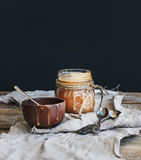 Salted caramel sauce in a rustic glass jar and brown ceramic cup on wooden desk Stock Photo