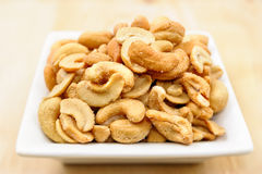 Salted cashew nuts on a white plate Royalty Free Stock Image