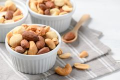Salted cocktail nuts on white wood stock photography