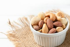 Salted cocktail nuts on white wood background royalty free stock photography