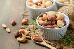 Salted cocktail nuts on wood background stock photo