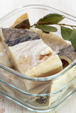 Salted cod fish in water in glass dish Stock Photo