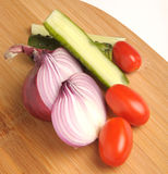 Salted cucumber, red cherry tomatoes and sliced red onion on Bamboo cutting board Royalty Free Stock Photography