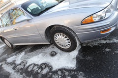 Salted driveway for new car. New car parked on an ice covered driveway. February ice storm protection stock photography