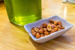 Salted frió los cacahuetes en una placa cerca de la cerveza verde en una tabla imagen de archivo libre de regalías