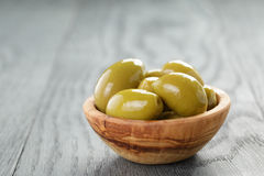 Salted giant green olives in olive bowl on wooden Stock Images