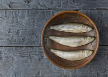 Salted herring in a clay bowl on wooden black table. The view from the top. Salted herring in a clay bowl on wooden rustic table. The view from the top. Natural Stock Images