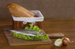 Salted herring, lettuce, olives, onions, bread basket wooden bac Stock Photo