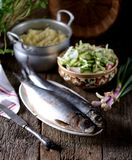 Salted herring with mashed potatoes and cucumber salad, radish and cabbage with olive oil on an old wooden background. Rustic styl Stock Image