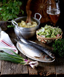 Salted herring with mashed potatoes and cucumber salad, radish and cabbage with olive oil on an old wooden background. Rustic styl Royalty Free Stock Photography