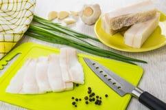 Salted lard, black pepper, knife on cutting board, napkin. Slices of salted lard, black pepper, kitchen knife on cutting board, napkin on wooden table Stock Image