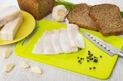 Salted lard, black pepper, knife on cutting board, rye bread. Slices of salted lard, black pepper, knife on cutting board, rye bread and garlic on wooden table Stock Image
