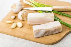 Salted lard, garlic and green onion on cutting board. Pieces of salted lard, garlic and green onion on cutting board on wooden table Stock Photo