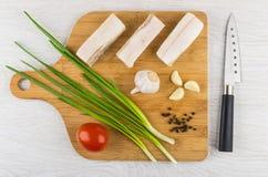 Salted lard, garlic, pepper, green onion, tomato on cutting boar. Pieces of salted lard, garlic, black pepper, green onion, tomato on cutting board and knife on Stock Photo