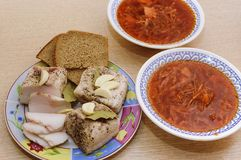Salted lard with pepper and bay leaf and black bread lies on a plate, next to it there are two plates with red borsch.. Close-up, stock photography