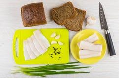 Salted lard, pepper on cutting board, bread, green onion, knife. Slices of salted lard, black pepper on cutting board, rye bread, green onion, knife and garlic Royalty Free Stock Photo