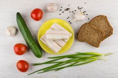 Salted lard in plate, bread, garlic, black pepper, vegetables. On wooden table. Top view Stock Photo