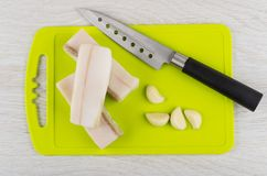 Salted lard, slices of garlic and knife on cutting board. Pieces of salted lard, slices of garlic and kitchen knife on cutting board on wooden table. Top view Royalty Free Stock Photography