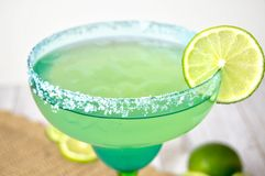 Margarita with lime slice. Salted margarita with lime slice in a festive blue and green glass against a wooden background royalty free stock photography