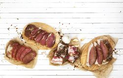 Salted meat, brisket, bacon, smoked ham on white wooden table. Top view Stock Photography