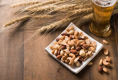 Salted mix cocktail nuts with beer and barley flower Royalty Free Stock Photography