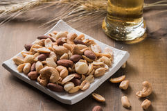 Salted mix cocktail nuts with beer and barley flower Royalty Free Stock Photo