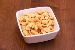 Salted nuts on bowl on wood Royalty Free Stock Images