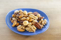 Salted nuts mix on a blue dish royalty free stock image