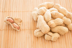 Salted peanuts on kitchen bamboo mat Royalty Free Stock Photos