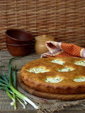 Salted pie with cottage cheese and young green garlic. On a wooden background stock photo