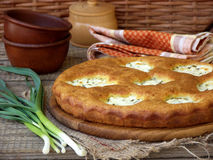 Salted pie with cottage cheese and young green garlic. On a wooden background royalty free stock images