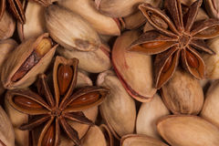 Salted pistachios and bright brown star anise. Two anise lie on the large bright pistachios Stock Images