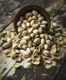 Salted pistachios are scattered from a wooden bowl on wooden rustic background,top view Stock Photography