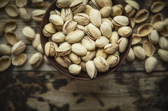 Salted pistachios in a wooden bowl on wooden rustic background, top view. Salted pistachios in a wooden bowl wooden rustic background, top view stock images