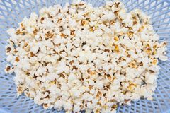 Salted popcorn grains. In a plastic bowl Stock Photo