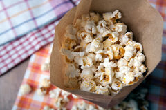Salted popcorn in a paper bag close up. Fresh salted popcorn in a paper bag close up royalty free stock photo