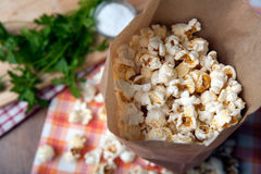 Salted popcorn in a paper bag close up. Fresh salted popcorn in a paper bag close up royalty free stock images