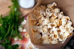 Salted popcorn in a paper bag close up. Fresh salted popcorn in a paper bag close up stock photos