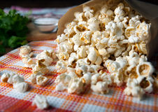 Salted popcorn in a paper bag close up. Fresh salted popcorn in a paper bag close up royalty free stock photos