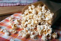 Salted popcorn in a paper bag close up. Fresh salted popcorn in a paper bag close up stock photo