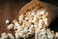 Salted popcorn in a paper bag on a wooden table. Close up royalty free stock images