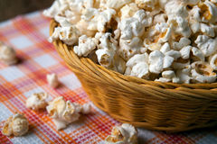 Salted popcorn in a wicker basket on a napkin Stock Images