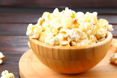 Salted popcorn in a wooden bowl on a wooden table. Salted popcorn in a wooden bowl on a wooden table Stock Images