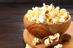 Salted popcorn in a wooden bowl on a wooden table. Salted popcorn in a wooden bowl on a wooden table Royalty Free Stock Image